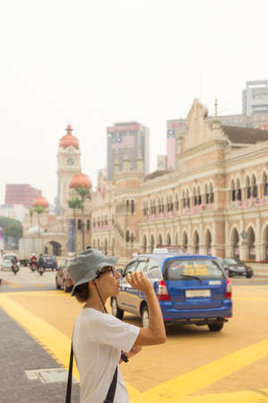 hot climate: Female european tourist with hat and glasses drinking a bottle of water in the traffic congested streets of Kuala Lumpur, Malaysia. Concept of staying hydrated in the hazy hot climate of the biggest south east asian cities. Stock Photo