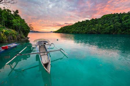 Adembenemende kleurrijke zonsondergang en traditionele boot drijvend op mooie blauwe lagune in de Togean (of Togian) Eilanden, Centraal-Sulawesi, Indonesië