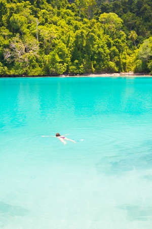the one person: One person snorkeling in the turquoise water of the remote Togean or Togian Islands, Central Sulawesi, Indonesia. Scenic lush green rainforest surrounding the transparent blue lagoon. Stock Photo
