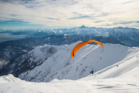stunning: Paraglider flying on snowy slope with bright orange kite. Stunning background of the italian Alps in winter season. Shot taken in backlight, unrecognizable person. Stock Photo