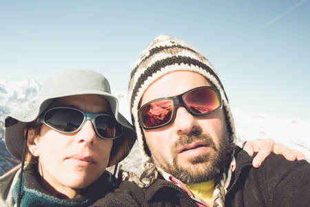self discovery: Adult european couple taking selfie in the beautiful natural landscape of the italian Alps in late winter season. Warm toned image, film vintage touch, desaturated. Stock Photo