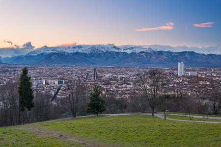 personal perspective: A personal perspective of Torino (Turin), Italy. Panoramic cityscape from above at dusk with scenic snowcapped mountain setting in the background. Stock Photo