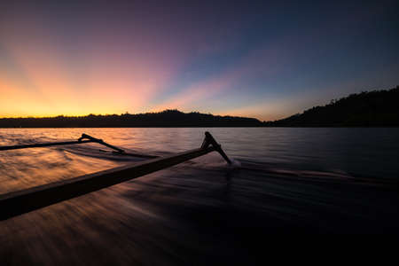 blurred motion: Sailing in the stunning colors of a breathtaking sunset in the remote Togean Islands (or Togian Islands), Central Sulawesi, Indonesia. Blurred motion on water surface.