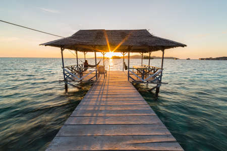 Tourist sitting on wooden jetty while watching a stunning sunrise on the sea. Togean (or Togian) Islands, Central Sulawesi, Indonesia. Wide angle view, pastel colored, soft light. Stock Photo