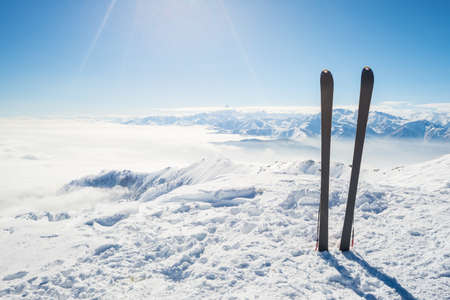 Pair of back country ski on the mountain summit. Shot in backlight, stunning panoramic view of the alpine arc with clouds covering the valleys below. Concept of success and conquering the top. photo
