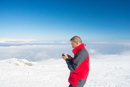 alpinist: Alpinist with phone in hand on the summit with majestic panoramic view of the italian Alps in winter season. Concept of sharing life moments using new technology even in hard condition.