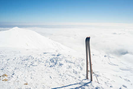 back country: Pair of back country ski on the mountain summit. Shot in backlight, stunning panoramic view of the alpine arc with clouds covering the valleys below. Concept of success and conquering the top. Stock Photo