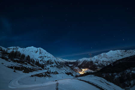 Aerial view of La Thuile village glowing in the night, famous ski resort in Aosta Valley, Italy. wonderful starry sky and majestic mountain landscape illuminated by the moon. Фото со стока