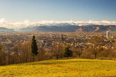personal perspective: A personal perspective of Torino (Turin), Italy. Pnaoramic view from above with lush green meadow in the foreground and scenic snowcapped mountain setting under wind storm in the background.