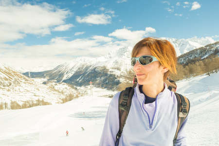 Adult female skier with backpack and sunglasses showing happiness on a sunny day in the ski resort of La Thuile, Aosta Valley. Concepts of spending free time on famous ski location. Toned image, decontrasted. photo
