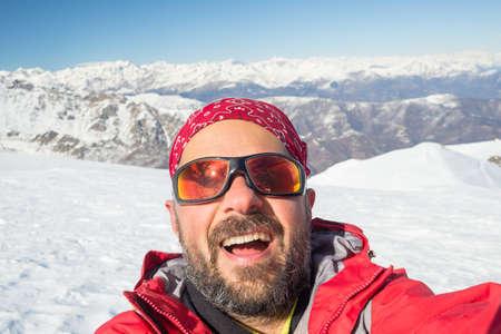 Volwassen Europese mens die selfie op besneeuwde helling met de mooie besneeuwde Italiaanse Alpen op de achtergrond. Natuurlijke kleuren. Stockfoto