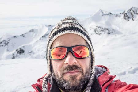 Volwassen Europese man met baard, zonnebril en hoed, die selfie op besneeuwde helling met de mooie besneeuwde Italiaanse Alpen op de achtergrond. Natuurlijke kleuren.