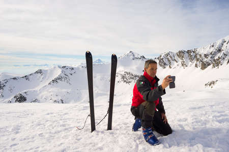 alpinist: Alpinist with smartphone in hand taking selfie on the mountain summit with majestic view of the snowcapped Alps. Concept of sharing life moments using new technology and wireless connection. Stock Photo