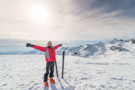 conquering: Male alpinist with arms outstretched near pair of back country ski on the mountain summit. Shot in backlight, stunning panoramic view of the alpine arc. Concept of success and conquering the top.