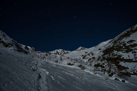 Wonderful starry sky and majestic snowcapped mountain landscape illuminated by the moon soft light. Glowing alpine hut in the distance. Nightscape in the italian Alps. photo