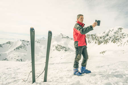ski resort: Alpinist taking selfie with smartphone with majestic view of the snowcapped Alps and pair of ski nearby. Concept of sharing life moments using new technology and wireless connection. Toned image, desaturated, old retro filter.