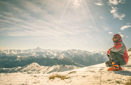 Alpinist on the mountain summit. Shot in backlight, stunning panoramic view of the alpine arc. Concept of success and conquering the top. Toned image, old retro touch. photo