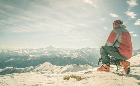 alpinist: Alpinist kneeling on the mountain summit. Shot in backlight, stunning panoramic view of the alpine arc. Concept of success and conquering the top. Toned image, old retro touch. Stock Photo