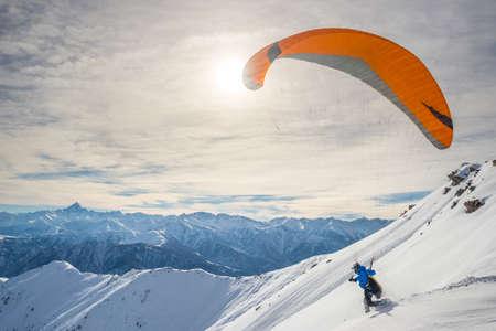 Paraglider draait op besneeuwde helling voor het opstijgen met fel oranje vlieger. Prachtige achtergrond van de Italiaanse Alpen in de winter seizoen. Schot genomen in tegenlicht, onherkenbaar persoon.