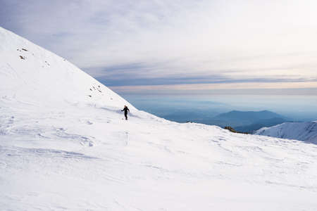 back country: Back country skier hiking uphill on snowy slope with scenic view in the background. Concept of conquering adversities and reaching the target. Italian Alps. Stock Photo