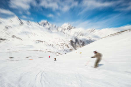 aosta: Speed skiing on snowy slope in ski the famous and scenic resort of La Thuile, Aosta Valley, Italy. Radial blurred motion effect applied. Unrecognizable people. Stock Photo