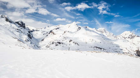 Stunning view of high mountain peaks in the italian alpine arc, in a bright sunny day and lot of candid snow. Ski resort of La Thuile and La Rosiere, on the border Italy France. Mont Blanc summit (4848 m) at the horizon. Stock Photo