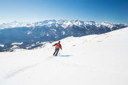 bardonecchia: One person skiing downhills on snowy slope in scenic ski resort of the italian Alps, with bright sunny day of late winter season. Majestic mountain peaks in the background.