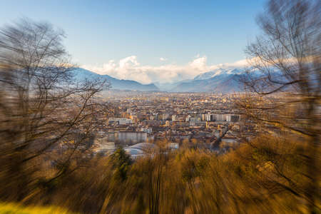 personal perspective: A personal perspective of Torino (Turin), Italy. Panoramic view from above with sparse trees in the foreground and scenic snowcapped mountain under wind storm in the background. Radial blurred edges applied. Stock Photo