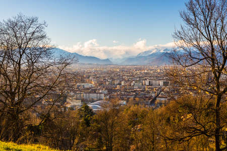 personal perspective: A personal perspective of Torino (Turin), Italy. Panoramic view from above with sparse trees in the foreground and scenic snowcapped mountain under wind storm in the background. Stock Photo