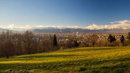 personal perspective: A personal perspective of Torino (Turin), Italy, at sunset. Panoramic view from above with lush green meadow in the foreground and scenic snowcapped mountain setting under wind storm in the background.