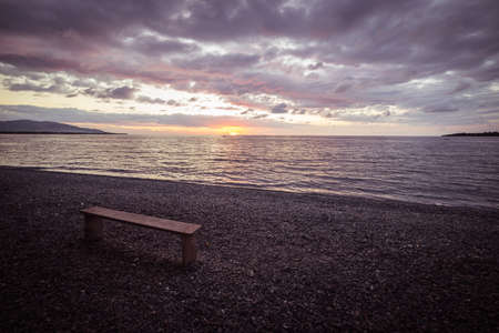 romantic sky: Empty wooden bench placed on pebbly beach with romantic sky at sunset on the coastline of Sulawesi, Indonesia Stock Photo