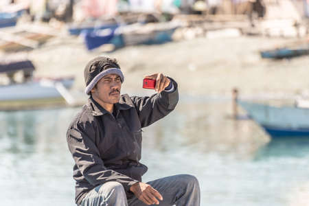 adult indonesia: Ampana, Sulawesi, Indonesia - August 23, 2014: Young male adult of togean ethnicity holding smartphone in hand for taking selfie in the port of Ampana. Concept of sharing life moments using new technology and wireless connection. Editorial