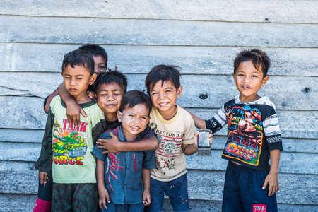 Boneoge, Sulawesi, Indonesië - 31 augustus 2014: Groep van niet-geïdentificeerde grappige kinderen tonen smartphone, glimlachen en kijken naar de camera in het dorp Boneoge, Sulawesi, Indonesië. Koude afgezwakt houten wand op de achtergrond.
