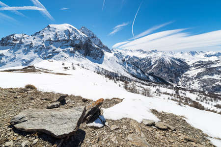 bardonecchia: Majestic wide angle view of snowcapped high mountain peaks in the italian alpine arc, in a bright sunny day of spring, near Via Lattea ski resort, Torino, Italy. Boulders and rocky terrain in the foreground.