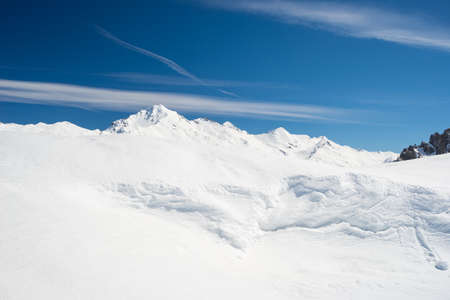 bardonecchia: Snowy slope shaped by the wind with snowdrift on the ridge and majestic view of snowcapped high mountain peaks in the italian alpine arc, in a bright sunny day of spring, Torino Province, Italy.