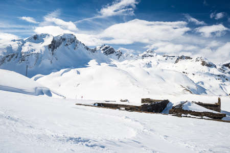 Stunning view of high mountain peaks in the italian alpine arc, in a bright sunny day. Ski resort of La Thuile and La Rosiere, on the border Italy France. Ruined mountain huts in the foreground.