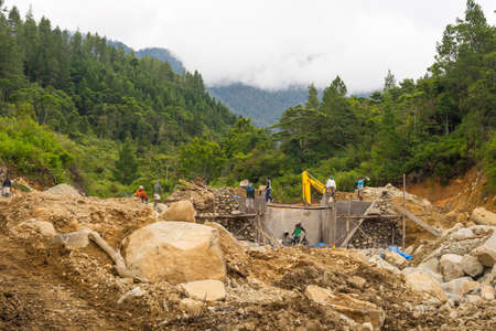 Mamasa, Sulawesi, Indonesië - 16 augustus 2014: Groep van lokale arbeiders die betrokken zijn bij de bouw van een kleine dam op stroom in de plaats van Loko, Mamasa Gewest, Sulawesi, Indonesië. Concept van de ontwikkelingslanden zonder de veiligheid voor mensen op het werk.