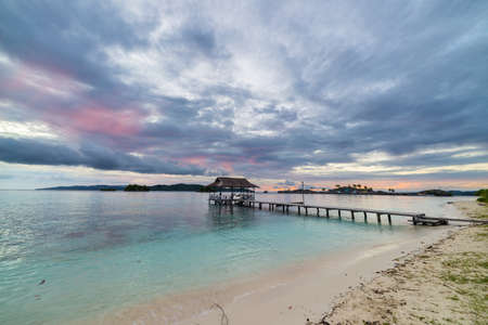 tourist resort: Romantic cloudy sky, coral spotted sea and wooden jetty in tourist resort in the remote Togian (Togean) Islands, Central Sulawesi, Indonesia. Long exposure taken at dusk with blurred motion.