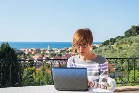 mature women: Mature lady with glasses and casual clothings working at laptop outdoors on terrace. Beautiful background of green hills and blue sky in a bright sunny morning. Natural daylight, real people.