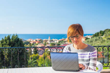 woman think: Mature lady with glasses and casual clothings working at laptop outdoors on terrace. Beautiful background of green hills and blue sky in a bright sunny morning. Natural daylight, real people.