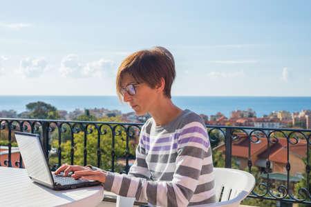 Rijpe dame met een bril en casual kleding die bij laptop buiten op het terras. Mooie achtergrond van groene heuvels en de blauwe hemel op een zonnige ochtend. Natuurlijk daglicht, echte mensen. Stockfoto