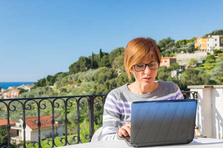 mujeres maduras: Se�ora madura con gafas y ropas informales que trabajan en la computadora port�til al aire libre en la terraza. Hermoso fondo de colinas verdes y el cielo azul en una ma�ana de sol brillante. La luz natural, la gente real. Foto de archivo