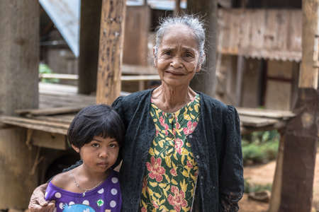 Taupe, Sulawesi, Indonesia - August 16, 2014: Portrait of a traditionally dressed senior women and a little girl looking at the camera in the village of Taupe, Mamasa region, West Tana Toraja.