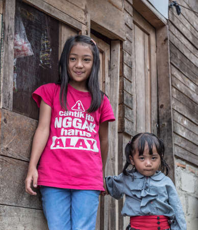 south asian ethnicity: Mamasa, Sulawesi, Indonesia - August 17, 2014: Couple of children of Toraja ethnicity smiling while looking at the camera in the countryside of Mamasa, West Tana Toraja.
