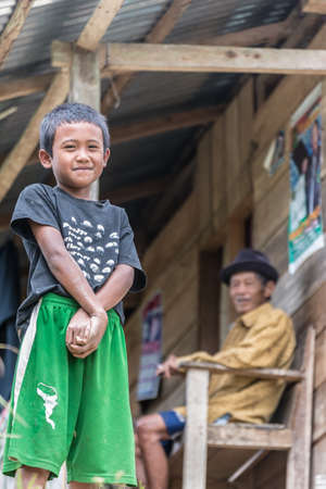 Osango, Sulawesi, Indonesia. - August 17, 2014: Selective focus on a little boy looking at the camera with a senior man in the background in the village of Osango, Mamasa region, West Tana Toraja.