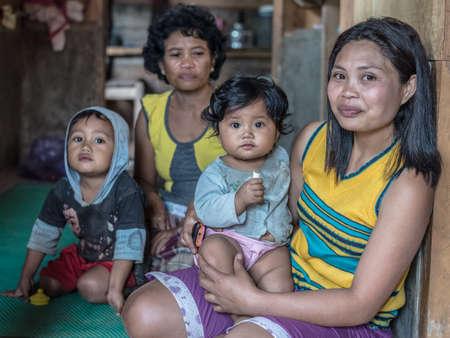 Loko, Sulawesi, Indonesië - 17 augustus 2014: Indoor portret van een leuke familie, twee volwassen vrouwen en twee baby's, in het dorp van Loko, Mamasa regio, West Tana Toraja. Redactioneel