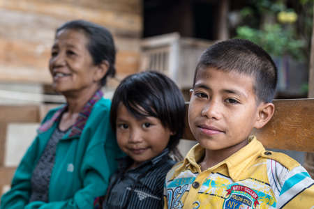 Loko, Sulawesi, Indonesia. - August 17, 2014: Selective focus on a cute boy looking at the camera with a little girl and a senior woman in the background in the village of Loko, Mamasa region.
