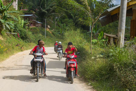 sulawesi: Mamasa, Sulawesi, Indonesia - August 18, 2014: Group of boys riding scooters on a country road in Mamasa, West Tana Toraja, South Sulawesi, Indonesia.
