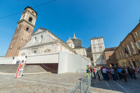 Torino, Italy - April 21, 2015: pilgrims waiting at the entrance of the Cathedral of Turin, Italy, for 2015 Holy Shroud Exhibition. Wide angle view from below.