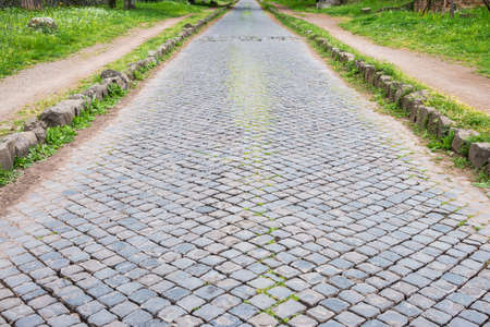 The ancient road of Via Appia Antica in Rome old town, topped with interlocking stones, one of the earliest and strategically most important Roman roads. It connected Rome to Brindisi, Apulia, in southeast Italy.